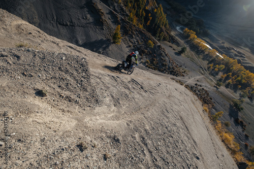 Obraz Extreme Rider climbing sand mountain top on off-road cross enduro motorcycle. Beautiful mountains landscape down on background, colourful autumn forest and river in sunshine - fototapety do salonu