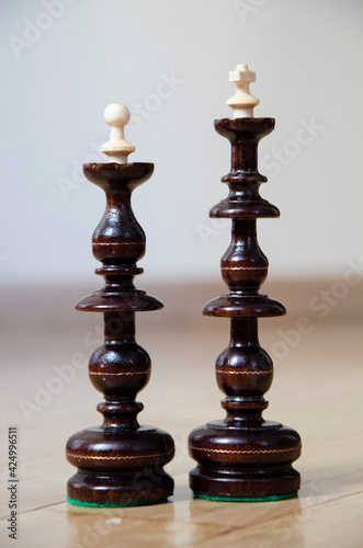 Fotografie, Obraz Chess board game, black wooden king and queen in focus
