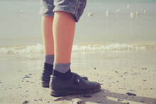 The Boy's Legs In Jeans Shorts, Socks And Dirty Shoes On The Seashore With Seagulls. Vintage Toned Photo.