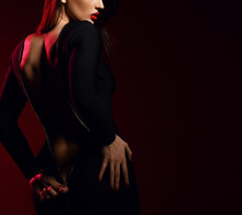 Backwards Silhouette Of Brunette Pretty Woman Model Standing And Zipping Up Sexy Black Dress With Naked Back Over Dark Red Background. Stylish Look And Sexual Games Concept