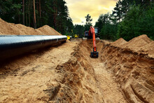 Excavator Dig Trench At Forest Area Sunset Background. Backgoe On Earthwork For Laying Crude Oil And Natural Gas Pipeline Or Water Main Pipes. Natural Gas Pipeline Construction