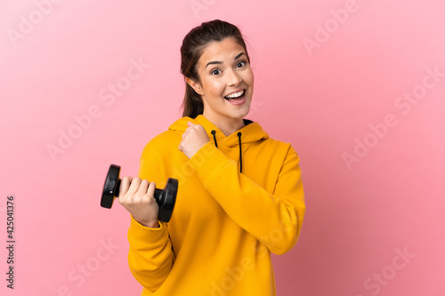 Fototapeta Young sport girl making weightlifting over isolated pink background celebrating