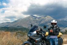 Magliano De Marsi, Italy - 26 July 2019: Biker Girl Sits On A Adventure Motorcycle Old Honda Transalp 600, On Background Riserva Naturale Orientata Monte Velino