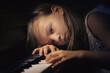 Dziewczyna w zadumie grająca na pianinie.