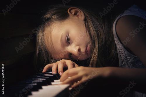 Obraz Dziewczyna w zadumie grająca na pianinie. - fototapety do salonu