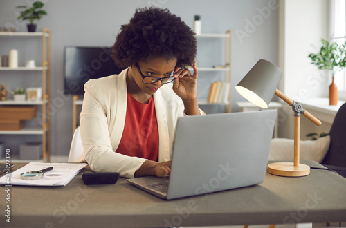 Young african american woman in eyewear carefully reading text on laptop computer device screen or typing answer on received letter, analyzing annual report sitting at desk in office Poster Mural XXL