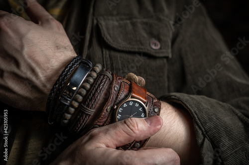 Fotografie, Obraz Stylish man wears wrist wooden and leather bracelets