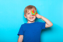 Laughing Caucasian Child Kid Boy Close One Eye Bright Colorful Lollipop Candy. Close-up Studio Shot.
