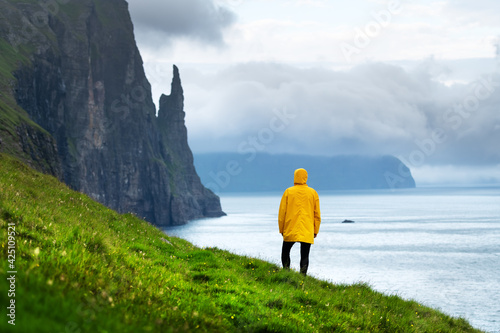 Tourist with backpack in yellow jacket looks at Witches Finger cliffs