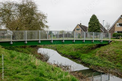 Obraz na plátne A metal footbridge over Werrington Brook, Cuckoos Hollow, Peterborough on a dull