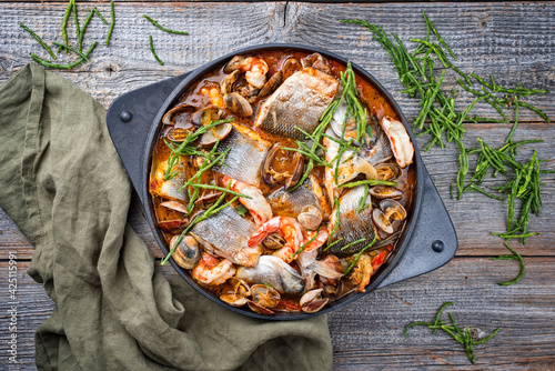 Modern style traditional Spanish seafood zarzuela de pescado with fish, king prawns and venus clams served with sea asparagus in red sauce as top view in design pot