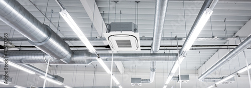 Photo Ceiling mounted cassette type air condition units with other parts of ventilation system (tubes, cables and vents) located inside commercial hall with hanging lights and other construction parts