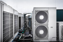 Square Air-conditioning Units On The Roof With Round Fan Grills. In The Background Gradually Receding Other Units And Parts Of Ventilation System Which Are Out Of Focus. Sky Is Uniformly Gray.
