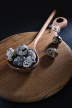 Quail Eggs In A Large Wooden Spoon On An Oak Kitchen Board. Easter Composition.