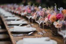 Wedding Banquet Wooden Table Decoration With Wine Glasses And Plates With Roses And Flower Bouquets Catering Decoration