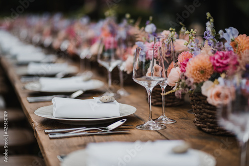 Tela Wedding banquet wooden table decoration with wine glasses and plates with roses