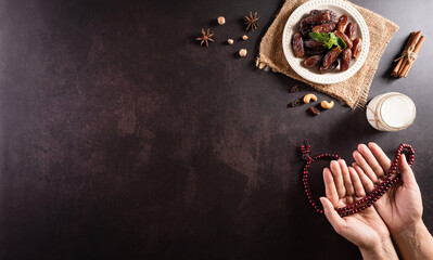 Ramadan Kareem background concept, Hands holding rosary bead with dates fruit and milk on dark stone background.