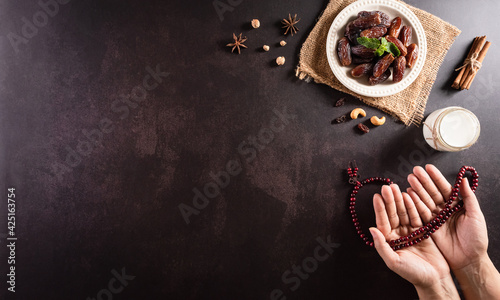 Fototapeta Ramadan Kareem background concept, Hands holding rosary bead with dates fruit and milk on dark stone background