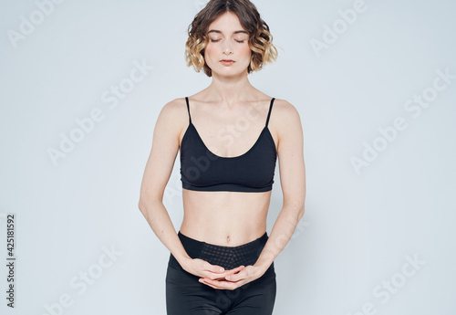 Tablou Canvas Woman in sportswear is engaged in fitness on a light background cropped view