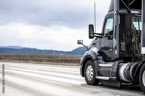 Tela Black stylish big rig day cab semi truck tractor transporting cargo in covered b