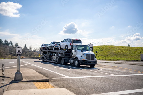 Fotografering Compact white big rig car hauler semi truck transporting cars on the two level m