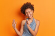 Isolated shot of curly haired woman keeps hand near mouth pretends singing into microphone wears fashionable clothes keeps palm raised isolated over vivid orange background. Stylish lady has fun