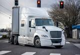 Fototapeta Uliczki - Powerful bonnet white big rig semi truck with dry van semi trailer turning on the city street crossroad with traffic light and crosswalk