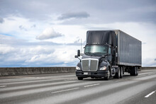 Powerful Stylish Black Big Rig Day Cab Semi Truck Deliver Commercial Cargo In Covered Dry Van Semi Trailer Driving On The Interstate Highway Road