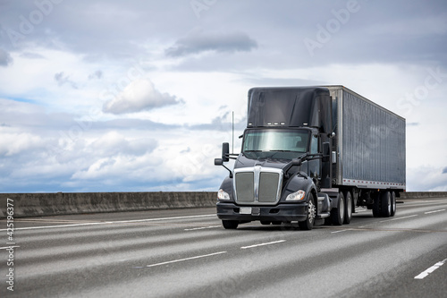 Fotografering Powerful stylish black big rig day cab semi truck deliver commercial cargo in co