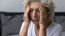 Stressed Frustrated Elderly Woman Feeling Strong Painful Headache, Holding Head, Touching And Massaging Temples With Closed Eyes. Migraine, Dizziness, High Blood Pressure, Healthcare Concept, Close Up