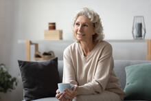 Smiling Pensive Mature Woman Holding Cup Of Tea Or Coffee, Sitting On Couch At Home, Looking Away, Thinking Over Good Insurance Opportunities, Future Leisure Time, Remembering Happy Life Moments.
