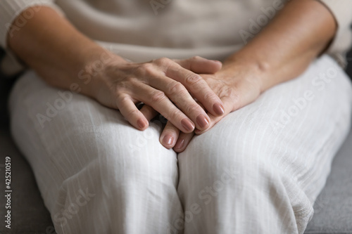 Fotografija Middle aged woman placing hands on lap, making stack of palms in waiting anxious position