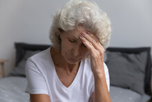 Upset Senior Lady Suffering From Headache Or High Blood Pressure, Getting Bad News, Grieving, Feeling Unwell. Desperate Frustrated Elderly 60s Lady Touching Head With Closed Eyes, Sitting On Bed.