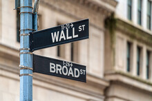 "Wall Street ""WALL ST"" Sign And Broadway Street Over American National Flags In Front Of NYSE Stock Market Exchange Building Background. The New York Stock Exchange Locate In Economy District"