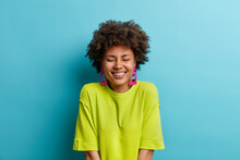 Studio Shot Of Positive Woman With Afro Hair Keeps Eyes Closed Smiles From Pleasure Shows White Perfect Teeth Wears Casual Green T Shirt And Earrings Isolated Over Blue Background. Emotions Concept
