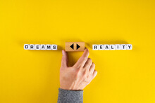 Hand Holds A Wooden Cube With Arrow Icon Between The Options Of Dreams Or Reality. To Chase The Dreams Or To Face The Reality Dilemma.