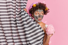 Surprised Female Has Curly Hair With Rubber Ducks Hides Naked Body Behind Shower Curtain Holds Sponge Looks Shocked Away Applies Beauty Mask Isolated Over Pink Background. Skin Care Concept.