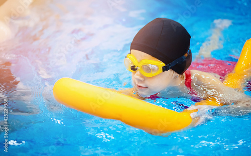 Fototapeta Little kid girl with glasses learning to swim with pool noodle obraz