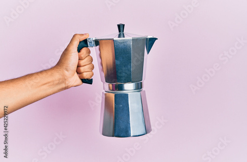 Hand of hispanic man holding coffee maker over isolated pink background Fototapet