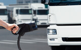 Fototapeta Kawa jest smaczna - Hand with charging plug on a background of electric truck. Concept