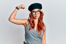 Young Redhead Woman Wearing Fashion French Look With Beret Strong Person Showing Arm Muscle, Confident And Proud Of Power