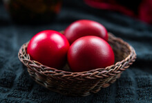 Close Up Of Red Dyed Easter Eggs In A Wicker Basket.