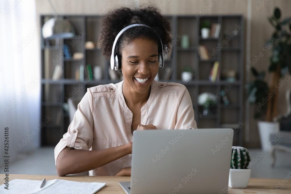 Fototapeta Smiling young African American woman in headphones work on laptop have webcam online digital conference. Happy millennial biracial female in earphones speak talk on video call on computer.