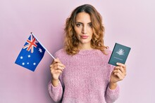 Young Caucasian Woman Holding Australian Flag And Passport Relaxed With Serious Expression On Face. Simple And Natural Looking At The Camera.