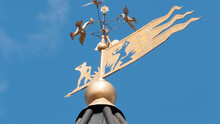 Architectural Accents And Details - Weather Vane. A Gold-colored Weather Vane - A Blacksmith With A Hammer And Anvil Against A Clear Blue Sky