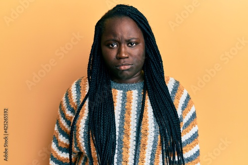 Billede på lærred Young black woman with braids wearing casual winter sweater depressed and worry for distress, crying angry and afraid