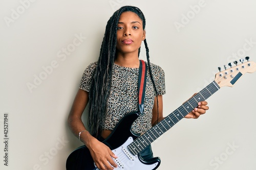 Fotografia, Obraz African american woman playing electric guitar relaxed with serious expression on face