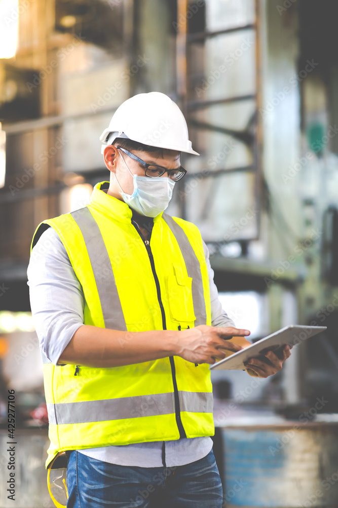 Fototapeta Worker man wearing face mask prevent covid-19 virus and protective hard hat. Engineer Operating lathe Machinery.