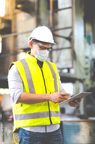 Obraz Worker man wearing face mask prevent covid-19 virus and protective hard hat. Engineer Operating lathe Machinery. - fototapety do salonu