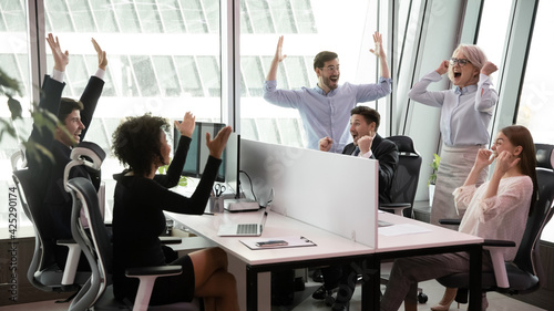 Fotografie, Obraz Overjoyed multiethnic employees colleagues feel euphoric celebrate company shared victory or job win